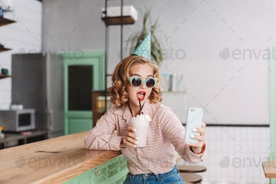 Beautiful lady in birthday cap sitting at the bar counter with milkshake taking cute selfie in cafe