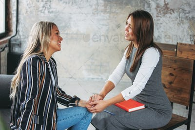Young successful women colleagues discuss joint project, coaching or psychotherapy in loft office