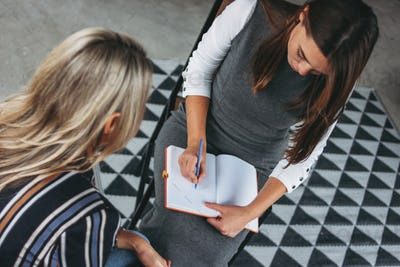 Young successful women colleagues discuss joint project, coaching or mentoring in loft office