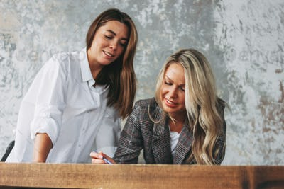 Young successful women colleagues discuss joint project, coaching in loft office