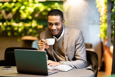 Afro guy drinking tea and using personal computer