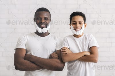 Black father and sun posing with foam beard and folded arms