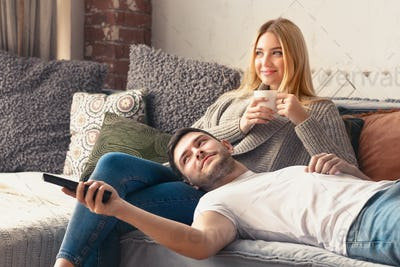 Young happy couple relaxing at home and watching tv