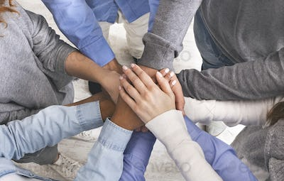 Joined hands in stack of unrecognizable people, closeup