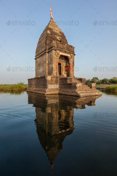 Small Hindu temple in the middle of the holy Narmada River, Maheshwar, Madhya Pradesh state, India