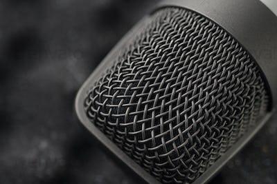 Gray studio condenser microphone on black soft foam of protective case. Macro shot