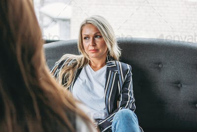 Upset young woman in office of psychotherapist or doctor