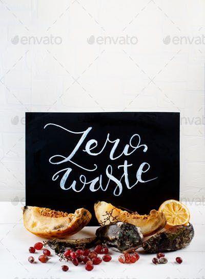Chalkboard with zero waste lettering and rotten fruits