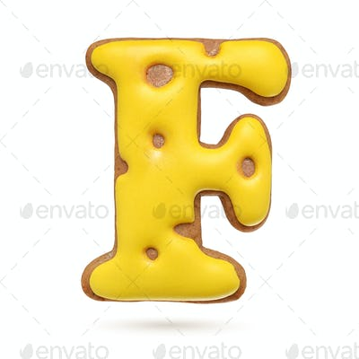 Capital letter F yellow gingerbread biscuit isolated on white.