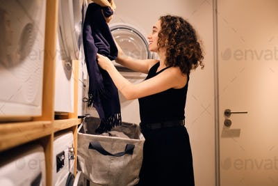 Pretty brunette girl happily loading clothes into washing machine in modern self-service laundry