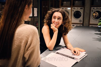 Attractive girl happily talking with friend waiting washing in self-service laundry