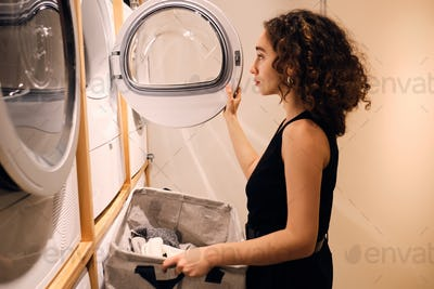 Beautiful girl loading clothes into washing machine in modern self-service laundry