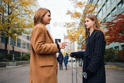 Two attractive casual girls talking standing with suitcase on street