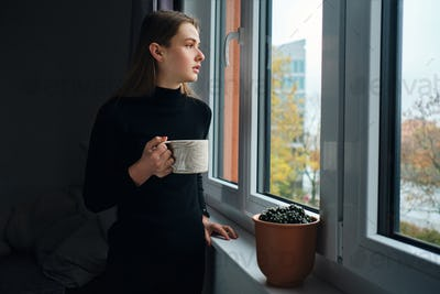 Side view of attractive girl holding mug while thoughtfully looking out the window at home