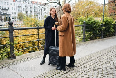 Two attractive stylish girls talking together standing with suitcase in park