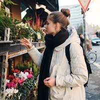 Side view of attractive casual girl in down jacket dreamily choosing flowers on city street