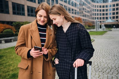 Two tourist girls happily looking information about city on cellphone with suitcase outdoor
