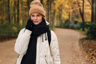 Unhappy casual girl sadly talking on cellphone standing in autumn park