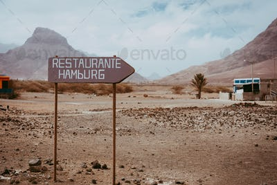 Old signpost in abandoned barren desert scenery. Volcano rugged on the horizon. Sao Vicente Cape