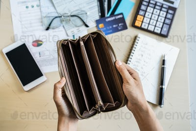 Stressed young woman open her empty wallet and calculating expenses at home