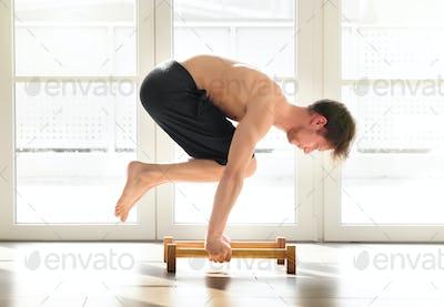 Young man doing a calisthenics crow pose