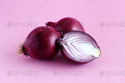 Purple onion on a light pink background