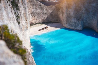 Navagio beach with turquoise blue sea water surrounded by huge white cliffs. Famous landmark