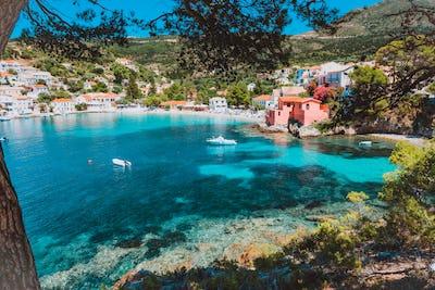 Assos village, Kefalonia, Greece. View on tourquise transparent water framed between green pine