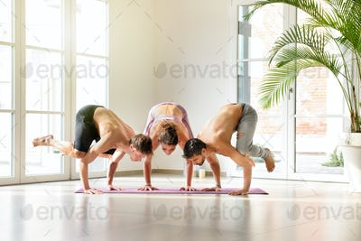 Group of three people doing a crow yoga pose