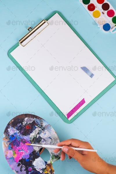 Female's hand of artist with brush before starting of painting picture on a pastel blue