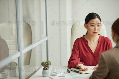 Asian Businesswoman Talking to Partner in Office