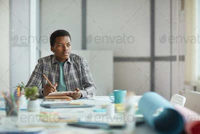 African-American Man Daydreaming at Workplace