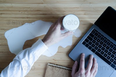 man spilling a glass of milk at work on his desk near his laptop