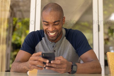 Young man smiling while using his mobile phone