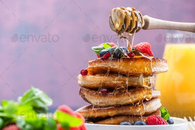 Pouring Honey on Pancakes Stack Topped with fresh Fruits. Shrove Tuesday Breakfast