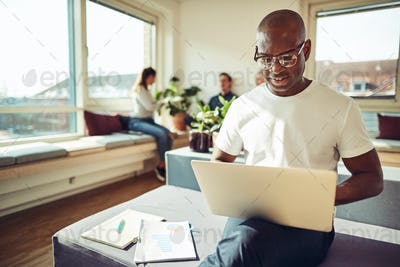 African businessman using a laptop with colleagues in the background