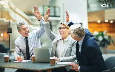 Mature businesspeople sitting at a table high fiving each other