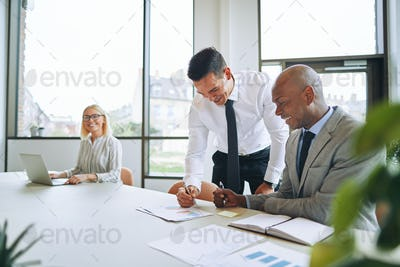 Two smiling businessmen discussing paperwork during a boardroom meeting