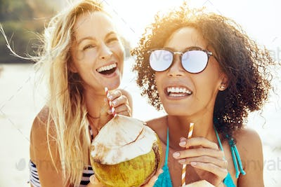 Laughing female friends walking along a beach drinking from coconuts
