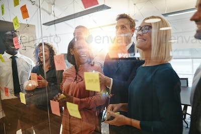 Diverse businesspeople laughing after brainstorming together in an office
