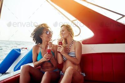 Smiling friends in bikinis sitting on a boat having drinks