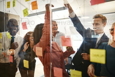 Cheering businesspeople high fiving during an office brainstorming session