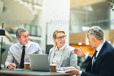 Three mature work colleagues talking business in an office lobby