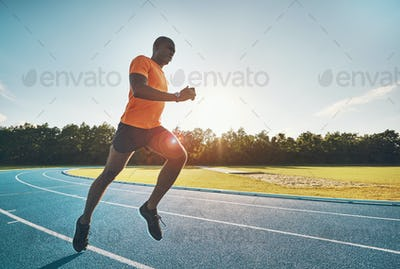 Fit young athlete racing alone down a running track