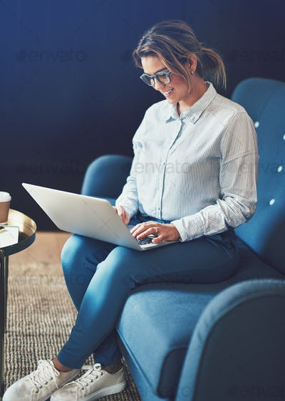 Young businesswoman smiling while sitting on a sofa working online