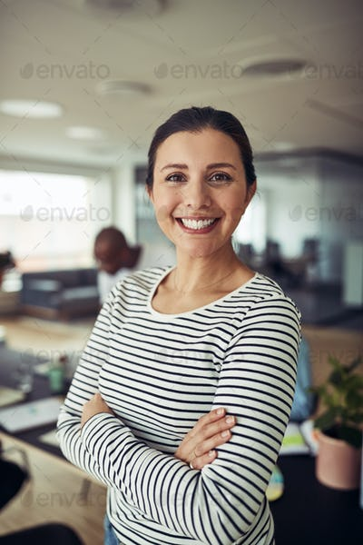 Smiling businesswoman standing with her arms crossed in an office