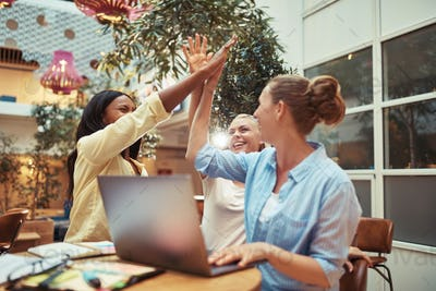 Diverse businesswomen laughing and high fiving in an office lounge