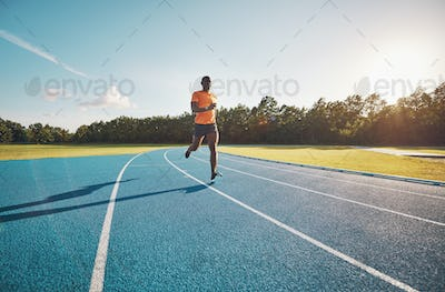 Focused young athlete running alone down an outdoor track