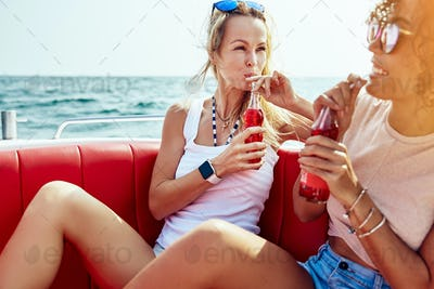 Two smiling friends sitting on a boat having drinks