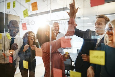 Businesspeople high fiving together with colleagues in an office